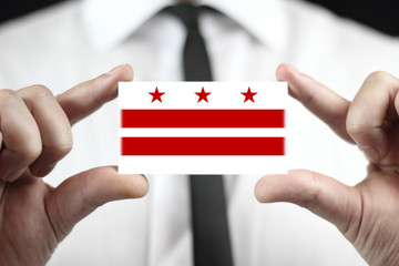 Businessman holding a business card with Washington DC Flag