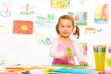 Little girl gluing poster