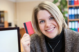 Young happy smiling woman paying by plastic card, at office
