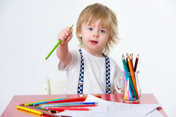 Cute kid holding one of his colorful crayons during art class