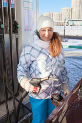 Young pretty woman refueling car with petroleum at winter season
