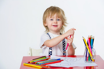 Adorable toddler drawing colorful paintings with bright pencils