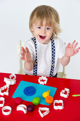 Cheerful kid playing with modelling clay and molding