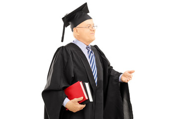 College professor in graduation gown holding book