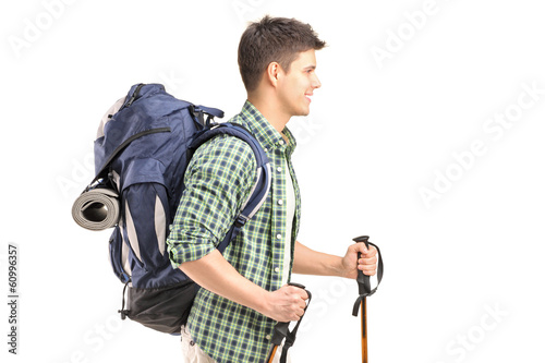 Hiker with backpack and hiking poles walking