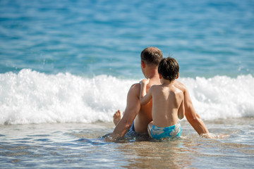 Father and son relaxing in ocean waves