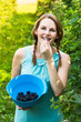 Young woman in blue dress picking blackberries