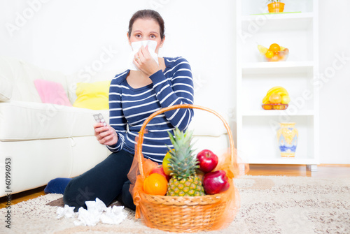 woman with a cold blowing nose and holding pills