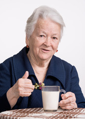 Healthy old woman with a glass of milk