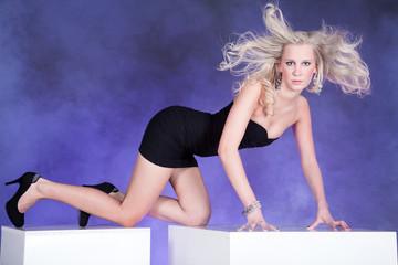 Hübsche blonde Frau auf Würfel