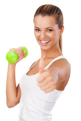 Fitness woman with weight showing thumb up