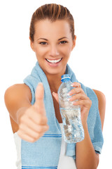 Fitness woman with bottle showing thumb up