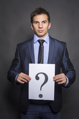 Businessman holding paper show question mark