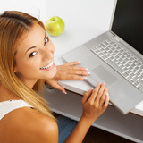 Smiling girl relaxing at home with laptop computer