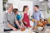 Lachende glückliche Familie beim Kochen mit Oma