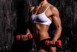 Muscled woman with barbells