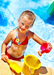 Child with bucket in swimming pool.