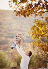 Father relaxing with his son in autumn nature