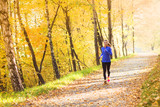 Active and sporty woman runner in autumn nature
