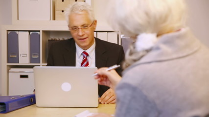 Consultant talking to elderly customer in office