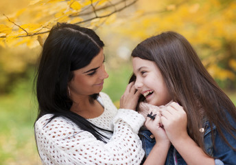 Mother and daughter are having fun in autum nature