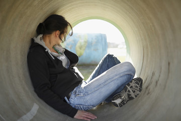 Young woman hiding in tunnel.