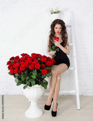 Beautiful brunette woman with red roses bouquet, leaning on old