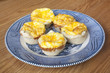 Mini onion and cheese quiche pies on a blue plate