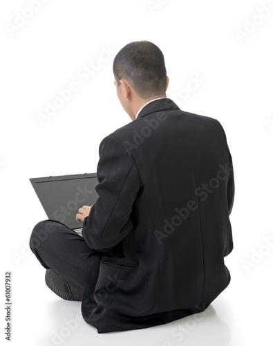 businessman using laptop on ground