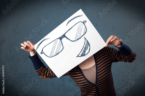 Woman holding a paper with smiley face in front of her head