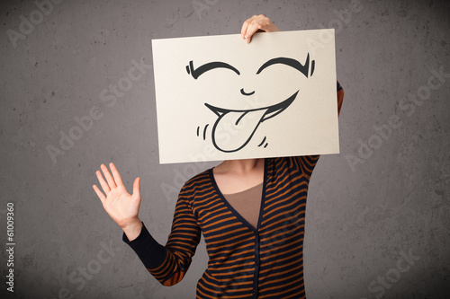 Woman holding a paper with cute smiley face on it in front of he