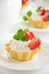 Tartlets with whipped cream and strawberries.