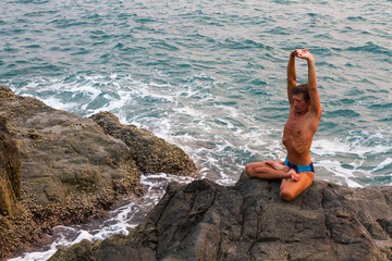A young man doing yoga on the beach.