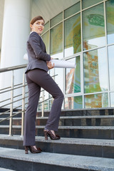 Businesswoman goes upstairs.