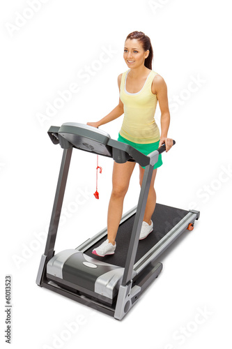 Young woman uses treadmill.