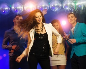 Group of happy young people dancing at night club