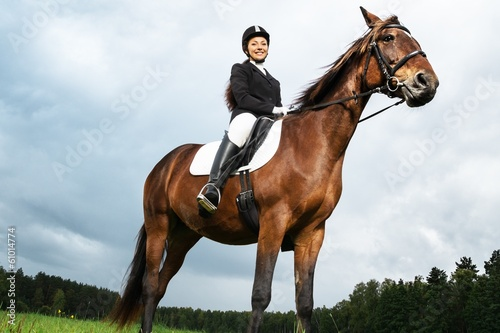 Cheerful young woman ridding horse in a field