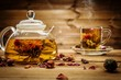 Teapot and glass cup with blooming tea flower inside