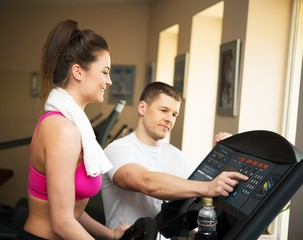 Trainer explains to a young woman how to use treadmill