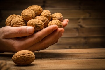 Hunan hands holding handful of walnuts over wooden table