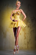 Beautiful ballerina in yellow tutu on point posing indoors