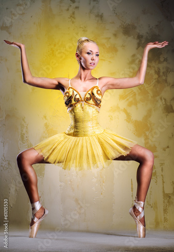 Beautiful ballerina in yellow tutu on point posing indoors