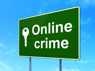 Security concept: Online Crime and Key on road sign background