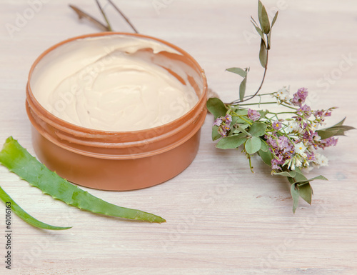 jar with body cream on wooden table
