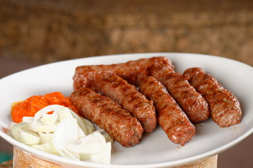 Traditional cevapcici with ajvar paste and onion