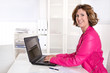 Berufstätige Mutter im Job - Portrait sitzend im Büro