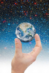 Hand holding planet earth in space.