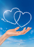 woman hand and heart shaped clouds on blue sky background poster