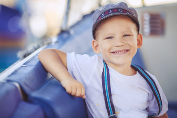 Cute sailor boy, about boats on the pier near the sea.