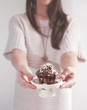 Young woman holding a muffin with chocolate and almonds